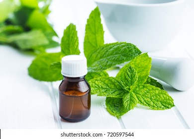 Bottle of essential mint oil and mint leaves.