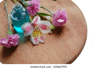 A bottle with essential oil of blue color and flowers. On a brown wooden round board. White background