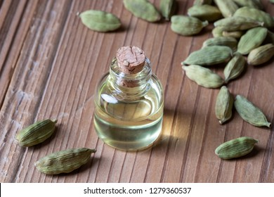 A bottle of essential oil with cardamon seeds