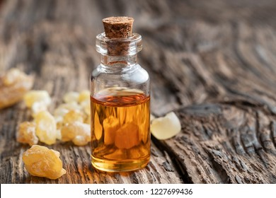 A bottle of essential oil with frankincense resin crystals on a rustic background