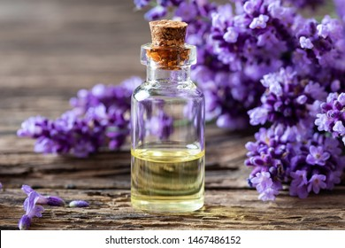 A bottle of essential oil with fresh blooming lavender twigs on a table