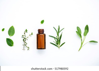 Bottle of essential oil with fresh herbal sage, rosemary, lemon thyme, thyme, green mint and peppermint setup with flat lay on white wooden table.