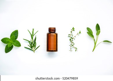 Bottle of essential oil with fresh herbal sage, rosemary, lemon thyme ,thyme ,green mint and peppermint setup with flat lay on white wooden table.