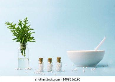 A bottle of essential oil with fresh juniper branches close-up on blue background. Homeopathic globules and glass bottles near a white plate. Alternative Homeopathy medicine herbs,  copy space.