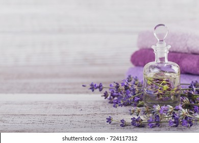 Bottle of essential oil and fresh lavender flowers on a white wooden background. Aromatherapy, spa and wellness concept