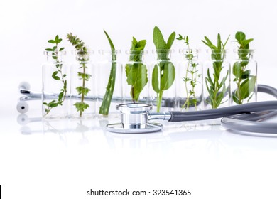 Bottle of essential oil with herb holy basil leaf, rosemary,oregano, sage,basil and mint with stethoscope on white background.