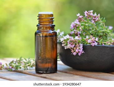 bottle of essential oil and lavender flowers on a table over green background
