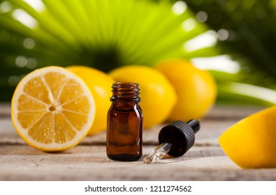Bottle of essential oil from lemons on wooden table and green leaves background - alternative medicine