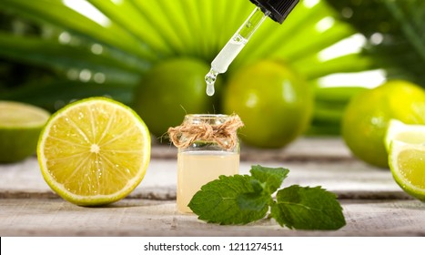 Bottle of essential oil from limes on wooden table and green leaves background - alternative medicine