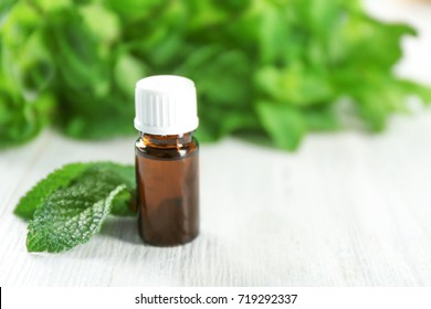 Bottle of essential oil and mint on wooden table