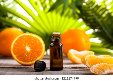 Bottle of essential oil from oranges on wooden table and green leaves background - alternative medicine