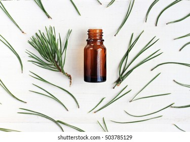 Bottle of essential oil, pine tree twigs and green needles scattered framed, top view, white wooden surface background.