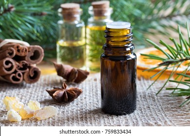 A bottle of essential oil with star anise, cinnamon sticks, frankincense resin, and pine and fir branches in the background