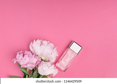 bottle of female perfume and bouquet of peony flowers on pink background. top view