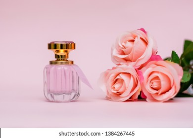 Bottle of female perfume with pink roses on pink color background