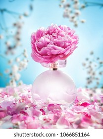 The bottle of flower perfume with a large peony on the lid stands on a table with many peony petals around. Blue blur background with small white flowers