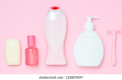 A bottle of fragrant perfume, lotion, shampoo, soap, razor. Products for the care of body, hair and personal hygiene on a pink pastel background.  Top view. Trend of minimalism. Flat lay.