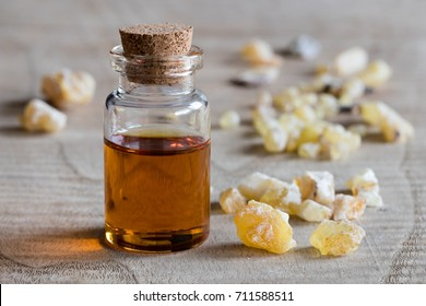 A bottle of frankincense essential oil on a wooden table, with frankincense resin in the background