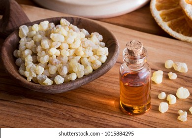 A bottle of frankincense essential oil with frankincense resin in the background