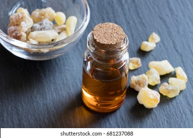 A bottle of frankincense essential oil with frankincense resin crystals in the background
