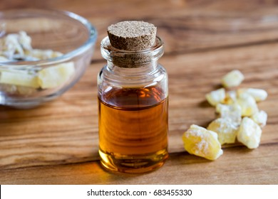 A bottle of frankincense essential oil with frankincense resin crystals in the background, on a wooden table