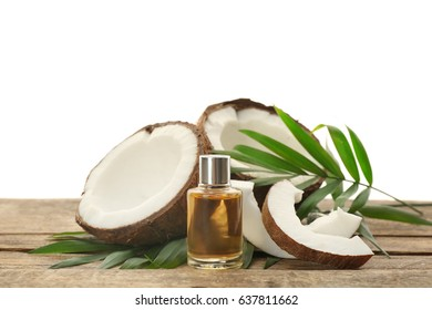 Bottle with fresh coconut oil and nut on wooden table
