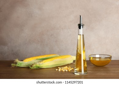 Bottle with fresh corn oil and cobs on table against color wall