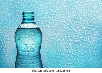 bottle of fresh water backlighting on background with water droplets
