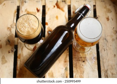 Bottle and full glasses of beer looking as a percent sign in a dirty wooden crate