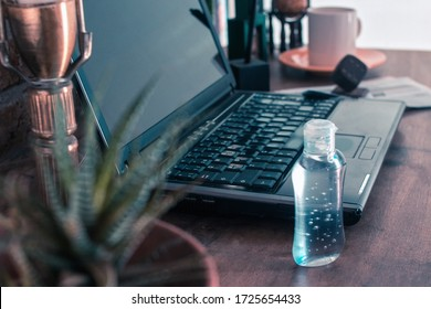 bottle of gel alcohol next to a laptop on a desk in a corner of the house as a home office