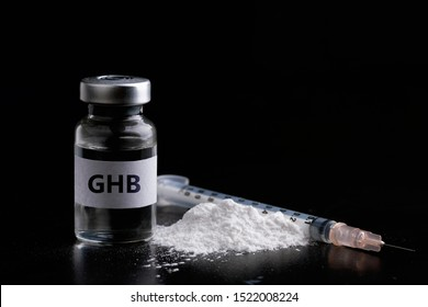 Bottle of GHB with a syringe in black background.Dangerous drug women