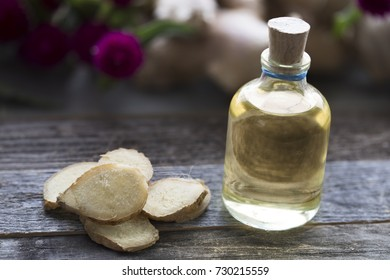 Bottle of ginger oil with ginger slices.