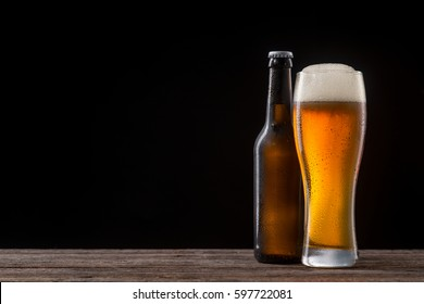 Bottle and glass of beer on a wooden table. Cold malted beverage with large head. Studio shot with black background and copy space to insert your text or picture.