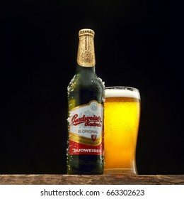 Bottle and glass of Budweiser beer on wooden table. Budweiser is one of the most popular domestic brands in the United States.