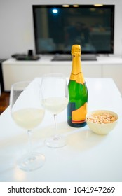 Bottle and glass of champagne in a living room