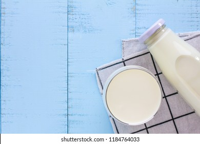 A bottle and a glass of milk on blue wooden background.