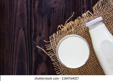 A bottle and a glass of milk on wooden background.