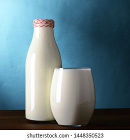 A bottle and a glass of milk are on the wooden table. Blue background. Square frame for instagram.