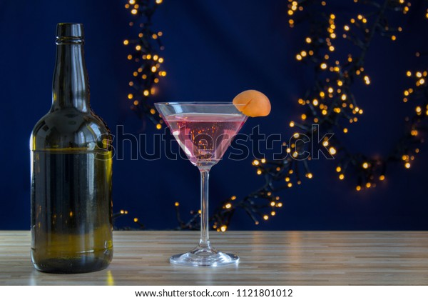 Bottle with glass pink alcohol and apricot