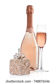 Bottle and glass of pink rose champagne with christmas decoration and gift on white background