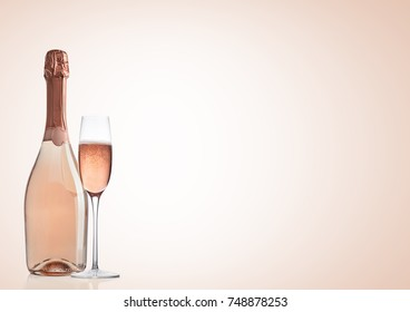 Bottle and glass of pink rose champagne on pink background