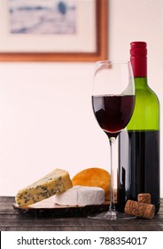 Bottle and glass of red wine with cheese selection with grapes restaurant table background