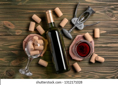 Bottle and glass of red wine with corkscrew on wooden background