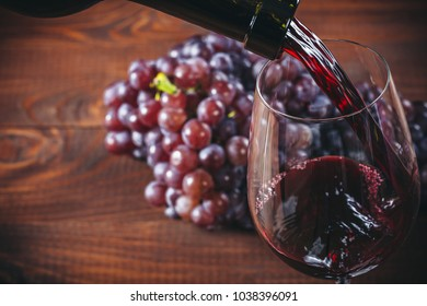 Bottle and glass of red wine, grape and cork on wooden background.