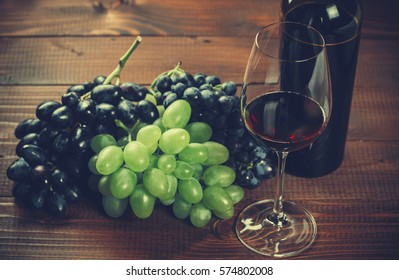 Bottle and glass of red wine and grape on wooden background.