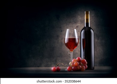 Bottle and glass of red wine with grapes on grange background