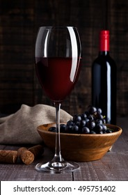 Bottle and glass of red wine with grapes in bowl on wooden board background