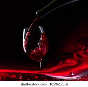 Bottle and glass of red wine on a black  background.