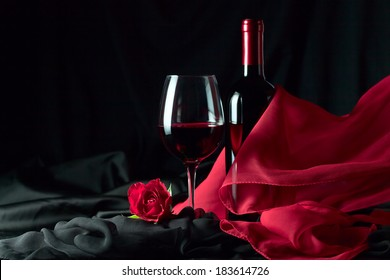 bottle and glass with red wine on  black background