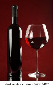 Bottle and glass of red wine on red background.